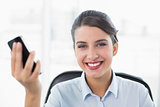 Content classy brown haired businesswoman holding a mobile phone