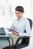 Smiling classy brown haired businesswoman using a tablet pc