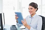 Amused classy brown haired businesswoman using a tablet pc