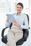 Happy classy brown haired businesswoman holding a tablet pc