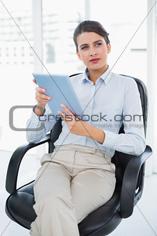 Thoughtful classy brown haired businesswoman using a tablet pc
