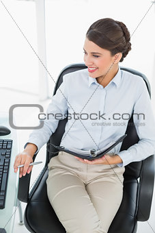 Amused classy brown haired businesswoman looking at her computer