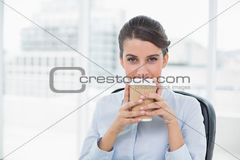 Calm classy brown haired businesswoman enjoying her coffee