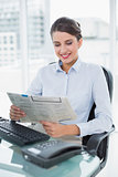 Pleased classy brown haired businesswoman reading a newspaper