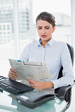 Frowning classy brown haired businesswoman reading a newspaper