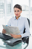 Stern classy brown haired businesswoman reading a newspaper