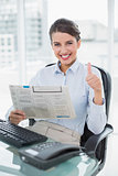 Cheering classy brown haired businesswoman reading a newspaper