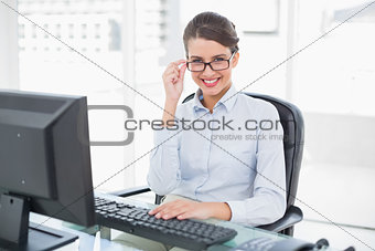 Charming classy brown haired businesswoman looking at camera over her glasses