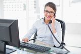 Content classy brown haired businesswoman answering the telephone