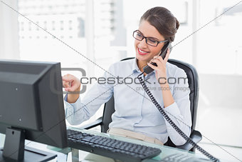Amused classy brown haired businesswoman answering the telephone