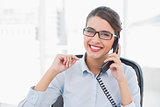Delighted classy brown haired businesswoman answering the telephone