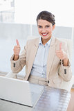 Content smart brown haired businesswoman giving thumbs up
