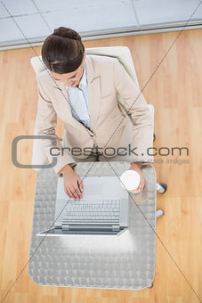 Attractive smart brown haired businesswoman using a laptop while holding a cup of coffee
