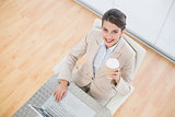 Joyful smart brown haired businesswoman holding a cup of coffee while using a laptop