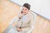 Amused smart brown haired businesswoman making a phone call