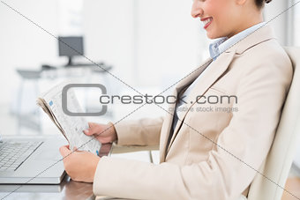 Close up of a pretty businesswoman reading a newspaper