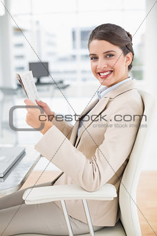 Attractive smart brown haired businesswoman reading a newspaper