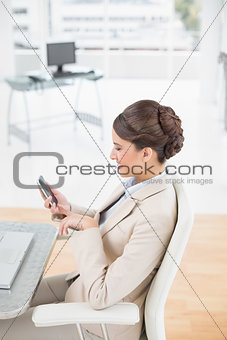 Charming smart brown haired businesswoman using a mobile phone