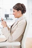Content smart brown haired businesswoman using a mobile phone
