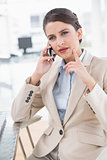 Stern smart brown haired businesswoman making a phone call