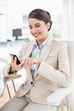Joyful smart brown haired businesswoman using a mobile phone
