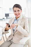 Pleased smart brown haired businesswoman using a mobile phone
