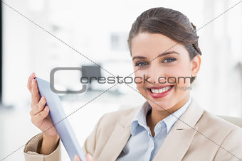 Amused smart brown haired businesswoman using a tablet pc