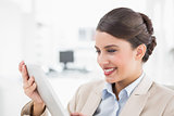 Amused smart brown haired businesswoman looking at a tablet pc