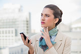 Thoughtful smart brown haired businesswoman holding a mobile phone