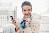 Delighted smart brown haired businesswoman holding a mobile phone