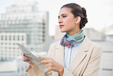Thinking smart brown haired businesswoman holding a newspaper