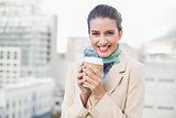 Smiling smart brown haired businesswoman holding a cup of coffee