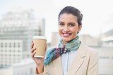 Pleased smart brown haired businesswoman holding a cup of coffee