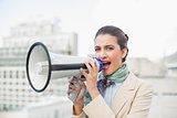 Irritated smart brown haired businesswoman using a megaphone
