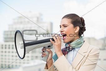 Angry smart brown haired businesswoman screaming in a megaphone