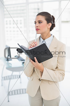 Thoughtful smart brown haired businesswoman filling an agenda