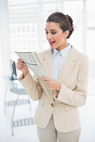 Surprised smart brown haired businesswoman reading a newspaper