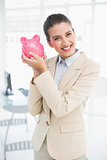 Happy smart brown haired businesswoman shaking a piggy bank
