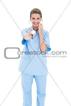 Amused brown haired nurse in blue scrubs playing with her stethoscope