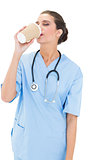 Calm brown haired nurse in blue scrubs enjoying her coffee