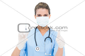 Beautiful brown haired nurse in blue scrubs holding a syringe and giving a thumb up