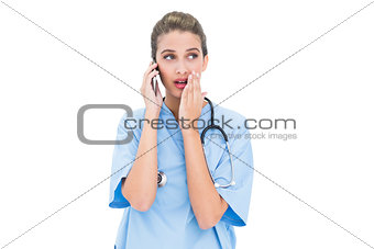 Astonished brown haired nurse in blue scrubs making a phone call