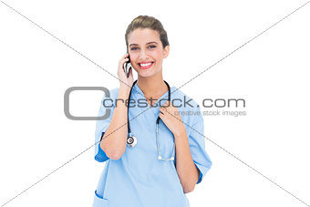 Smiling brown haired nurse in blue scrubs making a phone call