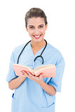 Happy brown haired nurse in blue scrubs holding a book