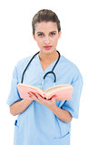 Stern brown haired nurse in blue scrubs holding a book