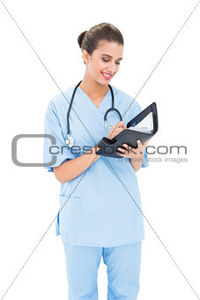 Attractive brown haired nurse in blue scrubs filling an agenda
