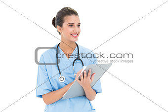 Attractive brown haired nurse in blue scrubs checking a report