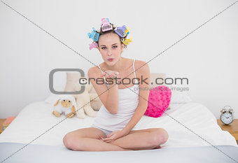 Seductive natural brown haired woman in hair curlers blowing a kiss to the camera