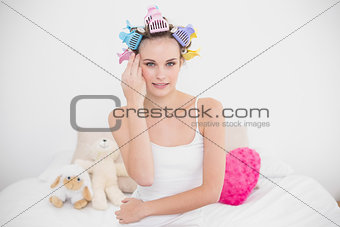 Calm natural brown haired woman in hair curlers touching her face