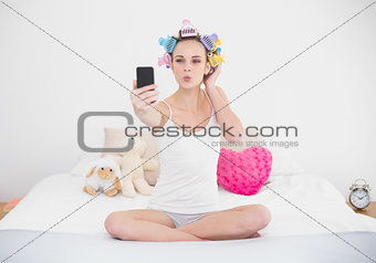 Pouting natural brown haired woman in hair curlers taking a picture of herself with mobile phone
